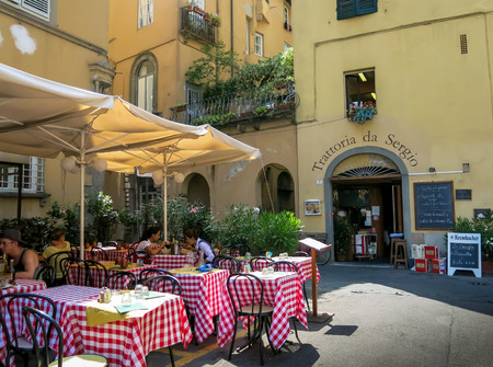 LUCCA, TUSCANY, ITALY - JULY 25, 2013: People on outdoor terrace of restaurant on Piazza Bernardini in Lucca, Tuscany, Italy