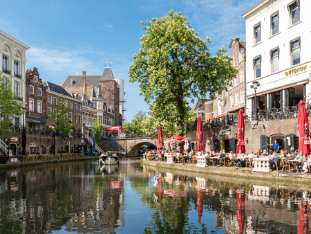 the medieval: UTRECHT, NETHERLANDS - MAY 21, 2015: Oudaen Castle and people on outdoor terrace of restaurants alongside Oudegracht canal in the city of Utrecht, Netherlands