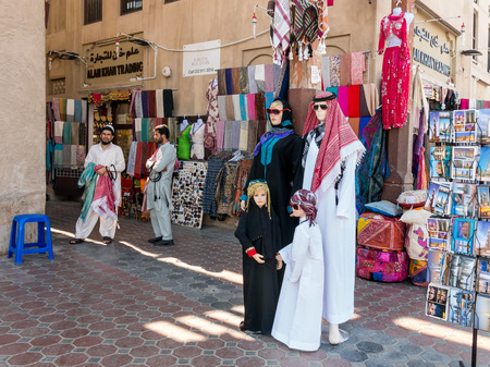 suq: DUBAI, UNITED ARAB EMIRATES - JAN 26, 2014: Shop and sellers in the ancient covered textile souq Bur Dubai in the old city centre of Dubai, United Arab Emirates