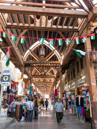 DUBAI, UNITED ARAB EMIRATES - JAN 26, 2014: People shopping in the ancient covered textile souq Bur Dubai in the old city centre of Dubai, United Arab Emirates