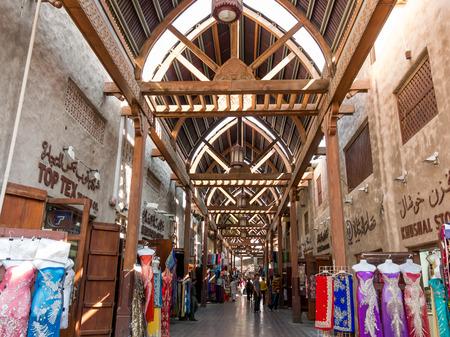 bur dubai: DUBAI, UNITED ARAB EMIRATES - JAN 26, 2014: Shops in the ancient covered textile souq Bur Dubai in the old city centre of Dubai, United Arab Emirates