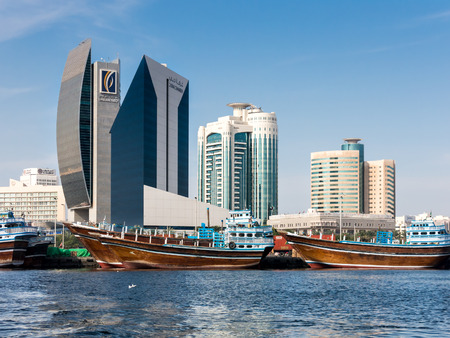 central chamber: DUBAI, UNITED ARAB EMIRATES UAE - JAN 26, 2014: Dhows and from left to right the buildings of National Bank of Dubai, Dubai Creek Tower and Al Reem Tower in Rigga Al Buteen Central Business District, Deira, the Creek in Dubai, United Arab Emirates