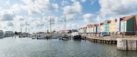 HELLEVOETSLUIS, NETHERLANDS - AUG 25, 2015: Panorama of harbour with windmill and colorful wharf houses in the city of Hellevoetsluis, Netherlands