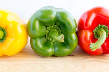 bell peppers: Three bell peppers in a row in different colours, yellow, green and red Stock Photo