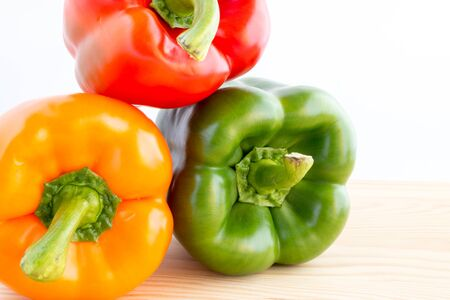 bell peppers: Three bell peppers in different colours, orange, red and green Stock Photo