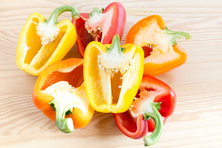 bell peppers: Stack of three halved bell peppers in different colours, orange, yellow and red Stock Photo