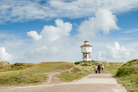 People walking in dunes and water tower of East Frisian island Langeoog, Lower Saxony, Germany Standard-Bild