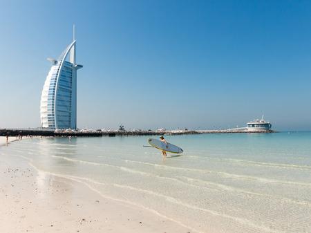 sails: Woman with surf board on Jumeirah Beach with Burj al Arab hotel in the background, Dubai, United Arab Emirates