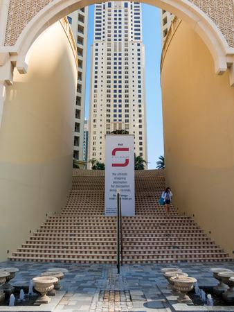 bajando escaleras: Mujer caminando por las escaleras del centro comercial El Paseo por el barrio de la Marina de Dubai, Emiratos �rabes Unidos