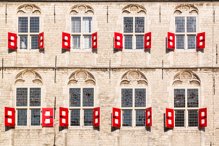 Facade with windows and red shutters of Town Hall on Market Square in Gouda, Netherlands