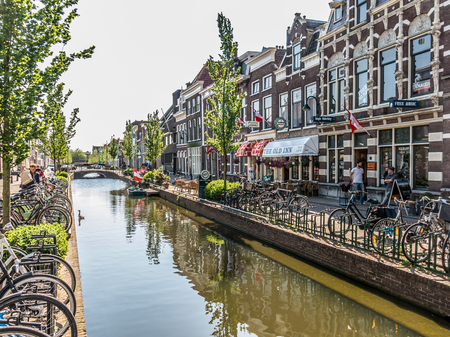 historical reflections: GOUDA, NETHERLANDS - JUNE 10, 2015: Bicycles and old houses on Turfmarkt canal in Gouda, Netherlands