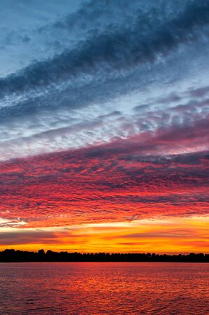 undulatus: Colourful cloudscape of altocumulus clouds at sunset, Lake IJssel, Netherlands Stock Photo