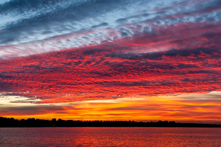 ijssel: Colourful cloudscape of altocumulus clouds at sunset, Lake IJssel, Netherlands Stock Photo