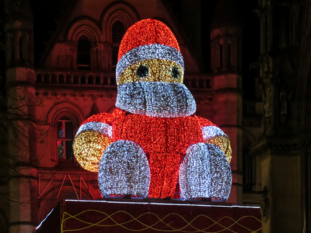 christmas in the city: Illuminated Big Santa on town hall at Christmas Market by night on Albert Square in Manchester, England, UK Stock Photo