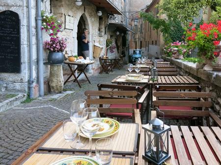 lazio: FIUGGI CITTA, LAZIO, ITALY - JULY 29, 2013: Narrow street and tables at outdoor restaurant in Fiuggi Citta, Lazio, Italy