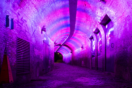 the lumen: Purple and pink illuminated Ganzemarkt tunnel to Oudegracht in the old city centre of Utrecht, Netherlands