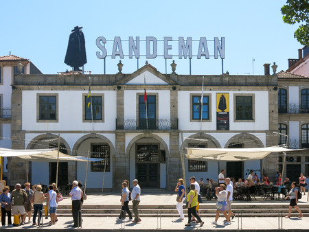 PORTO, PORTUGAL - AUG 20, 2013: Street scene with people walking in front of Port wine house and restaurant Sandeman on Cais de Gaia