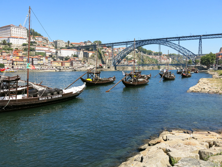 rabelo: Douro River with traditional rabelo boats and Dom Luis I Bridge. Ribeira district across the river. Porto, Portugal Editorial