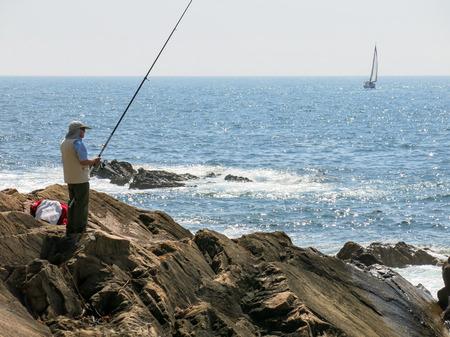pescador: OPORTO, PORTUGAL AUG - 21 de, 2013: Pescador de pesca en el Oc�ano Atl�ntico y la navegaci�n del velero en el mar frente a la costa de Foz cerca de Oporto, Portugal Editorial