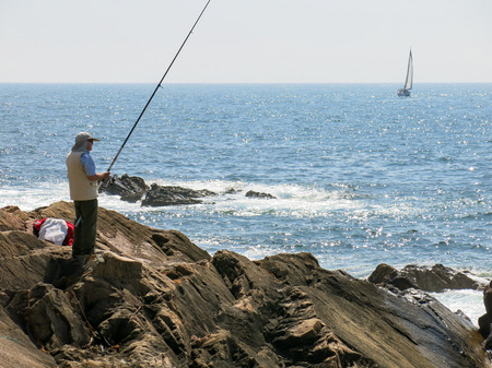 sailboat: PORTO, PORTUGAL - AUG 21, 2013: Fisherman fishing in Atlantic Ocean and sailboat sailing at sea off the coast of Foz near Porto, Portugal