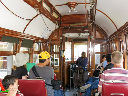 tramcar: PORTO, PORTUGAL - AUG 22, 2013: Tourists in vintage tramcar of heritage tram line in Porto, Portugal Editorial