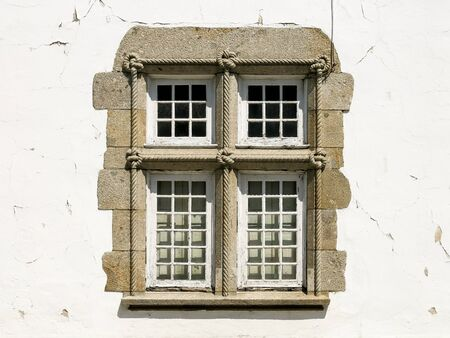 incorporates: Window decorated with knotted rope, detail on house in the town of Braga in Portugal. Example of Manueline style of architectural ornamentation that incorporates maritime elements.