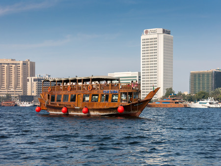 brook: Cruise with a traditional wooden dhow across the Creek and view of Deira district with Arbift Tower in Dubai, United Arab Emirates