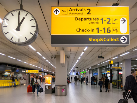 direction sign: Signs, clock and travellers in terminal of Schiphol Amsterdam Airport, Netherlands Editorial