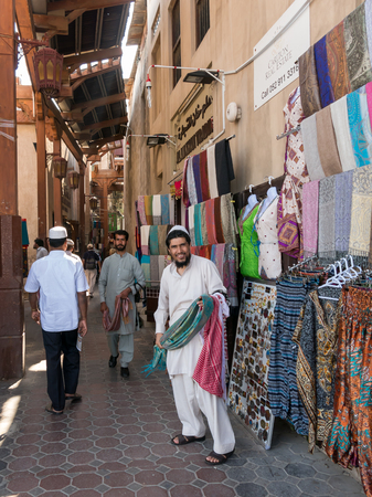 bur dubai: Shop salesmen in the ancient covered textile souq Bur Dubai in the old city centre of Dubai, United Arab Emirates