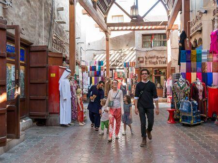bur dubai: Tourists in the ancient covered textile souq Bur Dubai in the old city centre of Dubai, United Arab Emirates Editorial