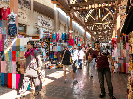 suq: Sellers and shops in the ancient covered textile souq Bur Dubai in the old city centre of Dubai, United Arab Emirates