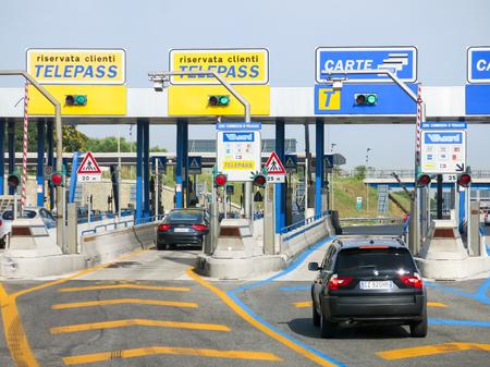 schlagbaum: Autos auf Autobahn Autostrade, Autobahn-Maut in Italien. Die Zahlung mit Telepass oder Karte. Editorial