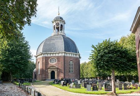 churchyard: BERLIKUM, NETHERLANDS - OCT 3, 2015: Dome church with churchyard in the Frisian town of Berlikum in Friesland, Netherlands