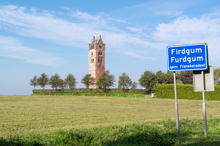 Tower of demolished church and town sign of Firdgum, small village in Friesland, Netherlands