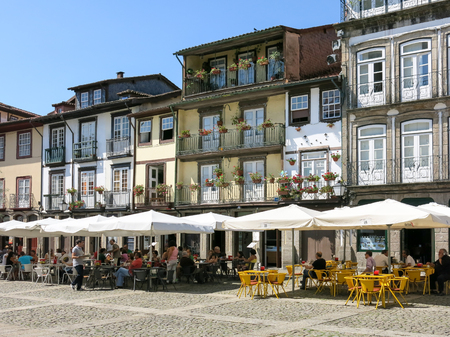 guimaraes: People relaxing on pavement cafes on Oliveira Square in the historical centre of Guimaraes, Portugal