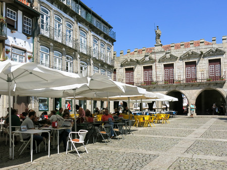 socialise: People relaxing on pavement cafes on Oliveira Square in the historical centre of Guimaraes, Portugal