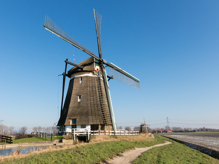 polder: Two windmills in a row in polder near Zevenhuizen in the province of South Holland, Netherlands Stock Photo