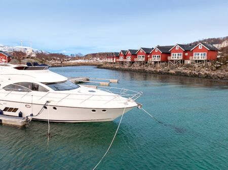 rorbuer: Speedboat and rorbu cabins with arctic blue sky light in Stokmarknes, Vesteralen, Norway