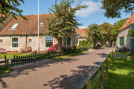 Street with old Dutch commander houses in the town of Hollum on the West-Frisian island Ameland, Netherlands