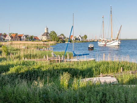 Dyke with houses, church, marina and boats on IJ lake in the village of Durgerdam in Amsterdam, Netherlands