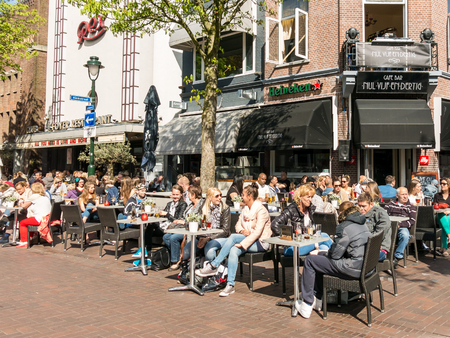 HILVERSUM, NETHERLANDS - APR 18, 2015: People having a break and enjoying a drink on an outdoor terrace of cafe bar restaurant on Groest in Hilversum, the Netherlands Editorial