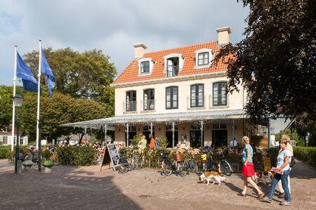 streetscene: Reeweg Street with tourists and hotel Graaf Bernstorff on the West Frisian island Schiermonnikoog in the Netherlands