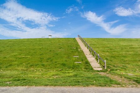 friesland: Stairway to top of dyke with picnic table. Dyke protects Friesland polder from  Waddensea, Netherlands