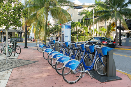 miami south beach: Bicycles parked in a row at city bike station on corner Collins Avenue and 14th Street in South Beach district of Miami Beach, Florida, USA