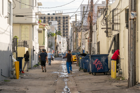 deprived: Street scene with local people, cars and waste containers in Collins Court in South Beach district of Miami Beach, Florida, USA