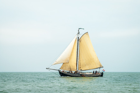 Traditional old Dutch wooden sailboat sailing on Wadden Sea, Netherlands
