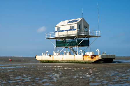 floatable: Birdwatch cabin on the tidal flats at low tide of the wetlands, Wadden Sea, Netherlands