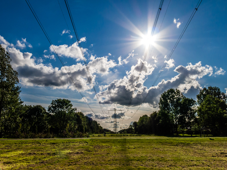 flevoland: Backlit high voltage electric power wires, Flevoland, Netherlands Stock Photo