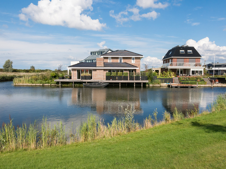 almere: ALMERE, NETHERLANDS - AUG 24, 2014: Waterfront houses in green residential suburb, Almere in the province of Flevoland near Amsterdam