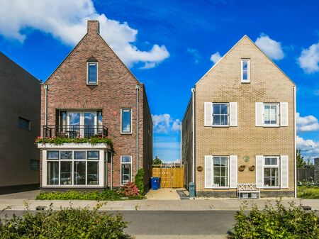 neighbourhood: ALMERE, NETHERLANDS - AUG 24, 2014: Two family houses in suburban neighbourhood street in Almere in the province of Flevoland near Amsterdam,  Netherlands Editorial